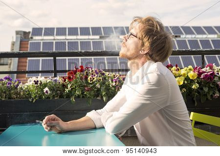 Young Man Sitting On Balcony And Smoking A Cigarette