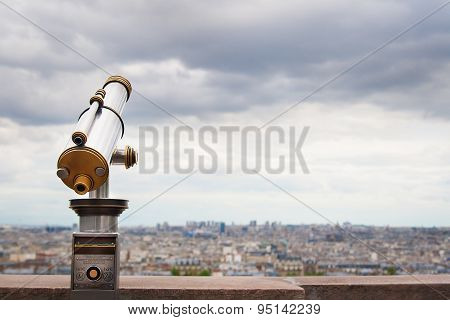 Telescope viewer and city skyline at daytime.