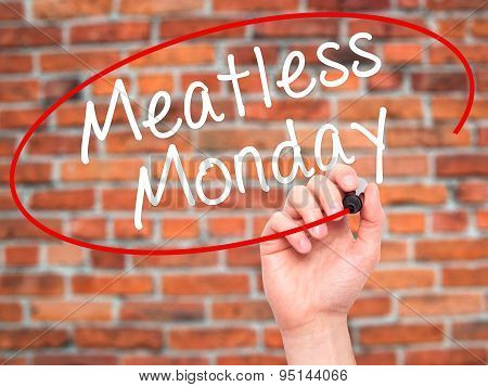 Man Hand writing Meatless Monday with black marker on visual screen.