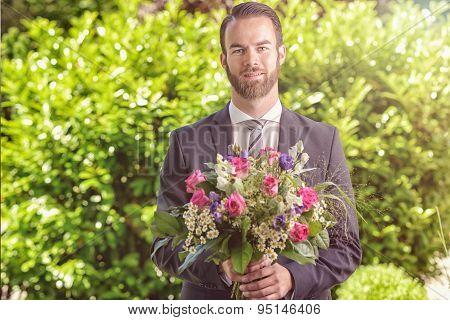 Handsome Man In A Suit Carrying Flowers