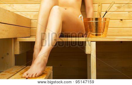 Woman Relaxing In Sauna. Female Legs.