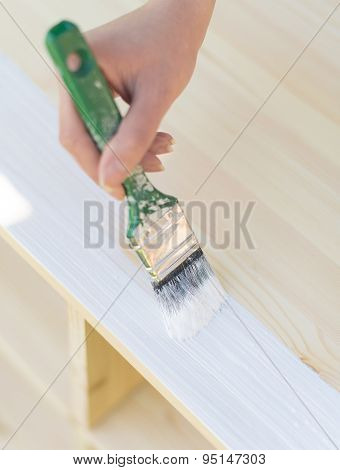 Female Hand With Brush Painting Wooden Furniture.