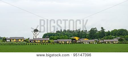 Modern Village. Traditional Windmill And Houses.