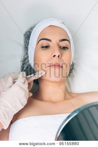 Pretty woman looking lips treatment in a mirror