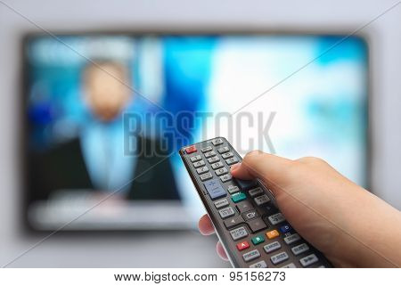Remote Control In Hand And Tv