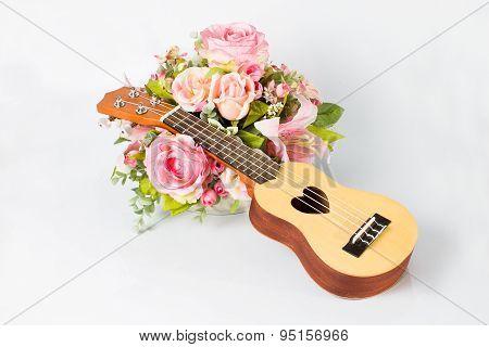 Ukulele and beautiful flower on white background