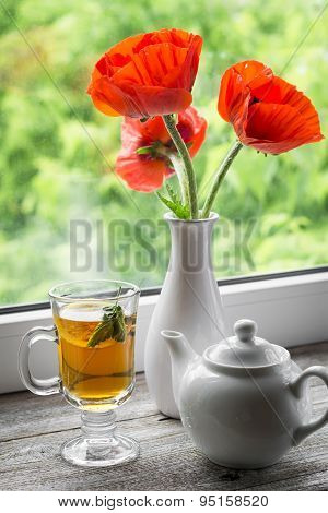 Green Tea With Lemon And Mint In A Glass Mug And Poppies In A White Vase On A Light Wooden Backgroun