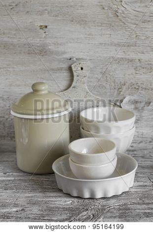 White Vintage Crockery - Enamelled Jug, Ceramic Bowl And Baking Dish On A Light Wooden Background