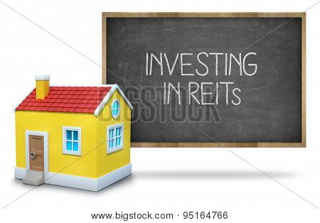 Investing in reits text on blackboard with 3d house