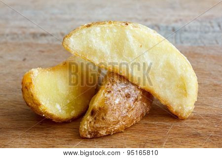 Detail Of Fried Potato Wedges Isolated On Rustic Wood Board.