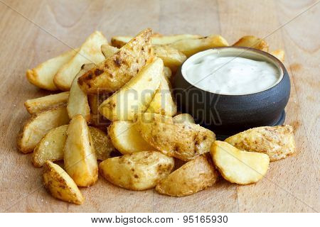 Heap Of Fried Potato Wedges On Wood Board With White Dip In Bowl.