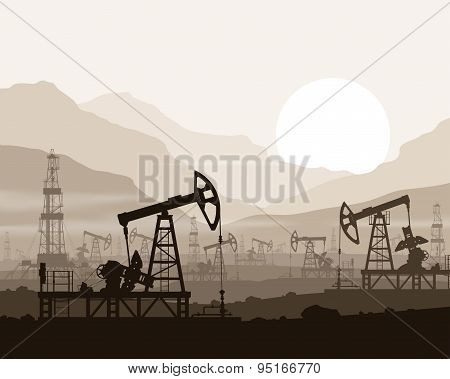 Oil pumps and rigs at oilfield over mountains.