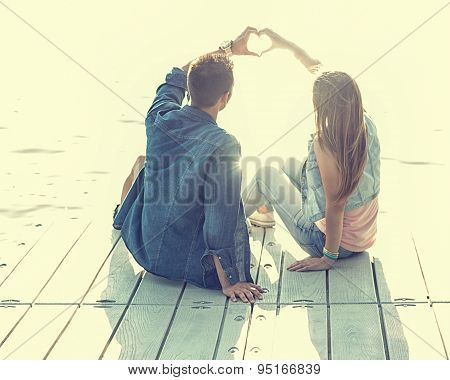 Couple in love sitting on the pier their hands show heart