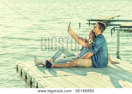 Couple in love sitting on the pier selfie