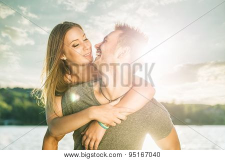 Couple in love embracing at the lake sun flare