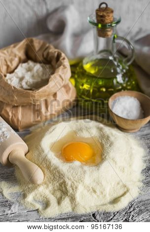 Flour, Olive Oil, Eggs - The Ingredients To Prepare The Dough For Pasta On A Light Wooden Background