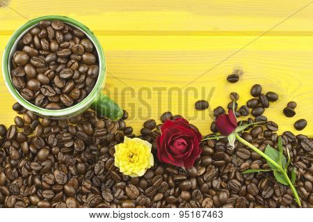 We love coffee. Roses resting on the coffee. Coffee beans, poured out on Yellow wooden table.