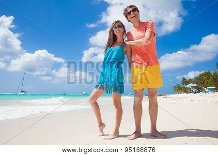 Closeup of happy young caucasian couple in sunglasses smiling at beach
