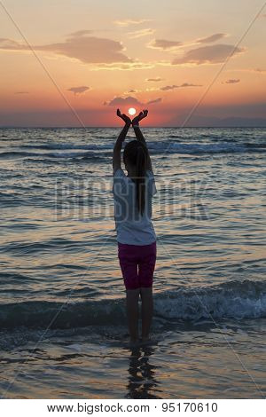 Young Girl Pretending To Hold A Sun In Her Hands