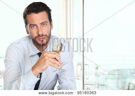 handsome man drinking a glass of sparkling wine white, at the bar