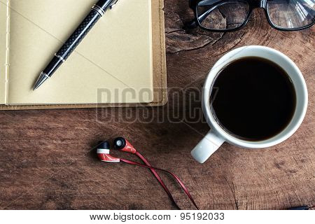 Close Up Of Earphone With Coffee And Notebook On Old Wooden Table