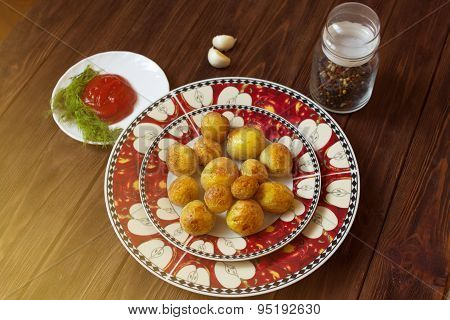 Baked Potatoes On Plate On Wooden Table