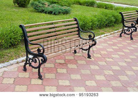 Brown Bench. garden. day light. tiles ground
