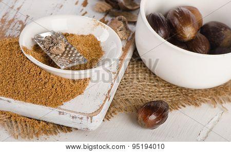 Organic Ground  Nutmeg On  A Wooden Cutting Board.