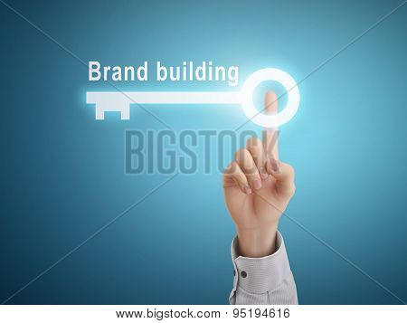 Male Hand Pressing Brand Building Key Button