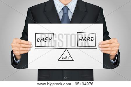 Businessman Holding Balance Between Ways Of Reaching A Solution