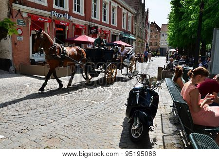 Bruges, Belgium - May 11, 2015: Tourists Visit Bruges In Traditional Horse Carriage Around The City.