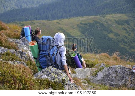 Tourists hiking in the mountains and enjoying view, travelin