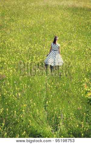 Rockabilly Girl With A White Petticoat Dress Walking Through A Wildflower Meadow