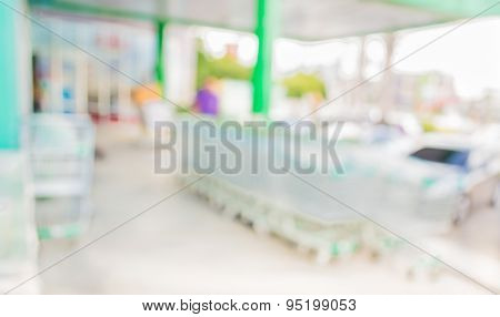 Blurred Image Of Shopping Mall And Parking For Background Usage .