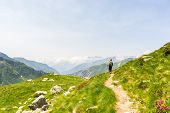 stock photo of italian alps  - One backpacker hiking uphill on footpath in the italian Alps - JPG