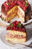 stock photo of sponge-cake  - Sliced raspberry sponge cake with fresh berries close up on a white plate - JPG
