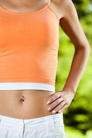 picture of pierced belly button  - Close up image of perfectly shaped female stomack - JPG