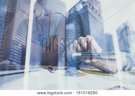 Closeup view of female hands touching screen digital tablet.Concept business people using mobile gadgets.Double exposure, modern skyscraper office building on blurred background.Horizontal