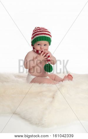 A seven month old baby boy sitting on a sheepskin rug. He is wearing a long red white and green striped stocking cap and chewing on the hat's tail. Shot on a white seamless background.
