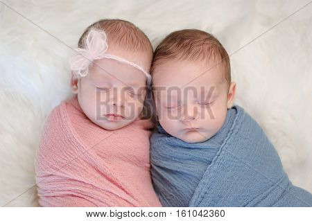 Two month old fraternal twin brother and sister babies swaddled in pink and blue wraps and sleeping on a sheepskin rug.