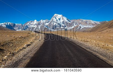 Himalayan mountain road (highway) in North Sikkim India from Lachen to Gurudongmar lake surrounded with snow capped peaks and vast barren lands.