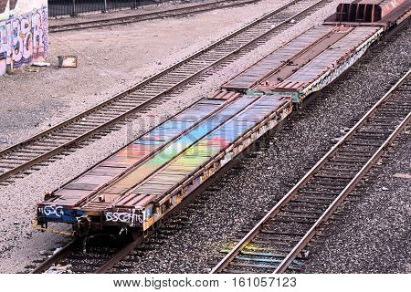 Flatcar which is a rail car that transports containers of cargo on a Freight Train taken at a rail stockyard in an inner city neighborhood