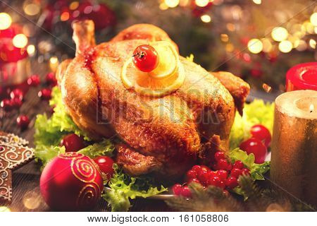 Christmas Dinner. Roasted Chicken Winter Holiday table served, decorated with candles. Roasted turkey, table setting