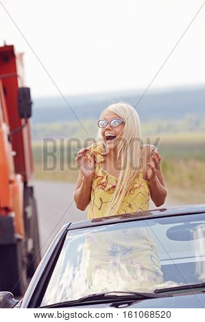 Portrait of girl sitting in convertible car, frightened and surprised because of truck that suddenly outrunning her car