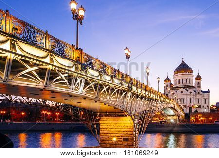 Moscow Christ the Savior Cathedral and Patriarchal pedestrian bridge with night illumination in the evening