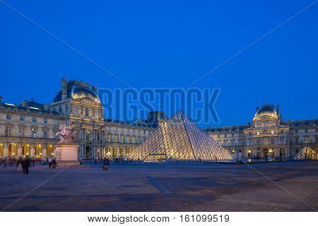 PARIS, FRANCE - DECEMBER 09, 2016: View of famous Louvre Museum with Louvre Pyramid at evening. Louvre Museum is one of the largest and most visited museums worldwide.