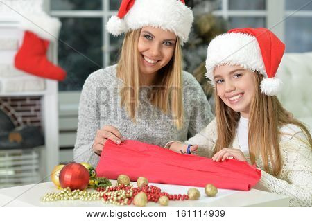 Portrait of two happy sisters preparing for Christmas at home
