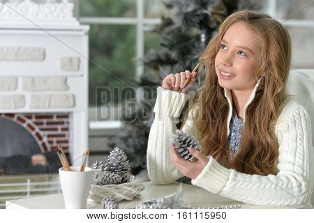 Portrait of happy teen girl with Christmas decorations sitting at the table at home