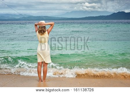 Portrait of an attractive girl wearing white dress on a beach before the rain on a background of the dramatic sea and islands. Beach sunset nature evening. concept love romance.