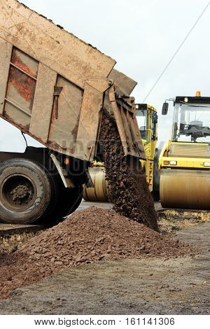 Construction truck unloads ground to the construction site and road widening.